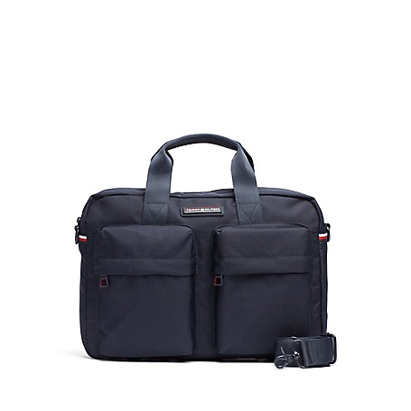Tommy Hilfiger Tommy Nylon Laptop Bag - Tommy Navy Tommy Hilfiger Men's Bag. Safely Tote Your Laptop In Our Bag With Dual Exterior Pockets To Keep Your Essentials At The Ready. Styled In Durable Nylon To Outlast The Daily Grind And Featuring A Genius Exterior Pocket That Zips Opens At The Bottom, Allowing The Bag To Slide Over The Handle Of Your Upright Suitcase.  Laptop Bag Silhouette In Nylon. 12'' (H) 16'' (L) 4'' (W) Zip Closure, Interior Pockets, Lined. Spot Clean. Imported.